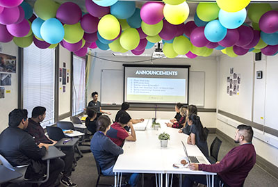 Youth at Digital NEST in a workshop with balloons floating above them